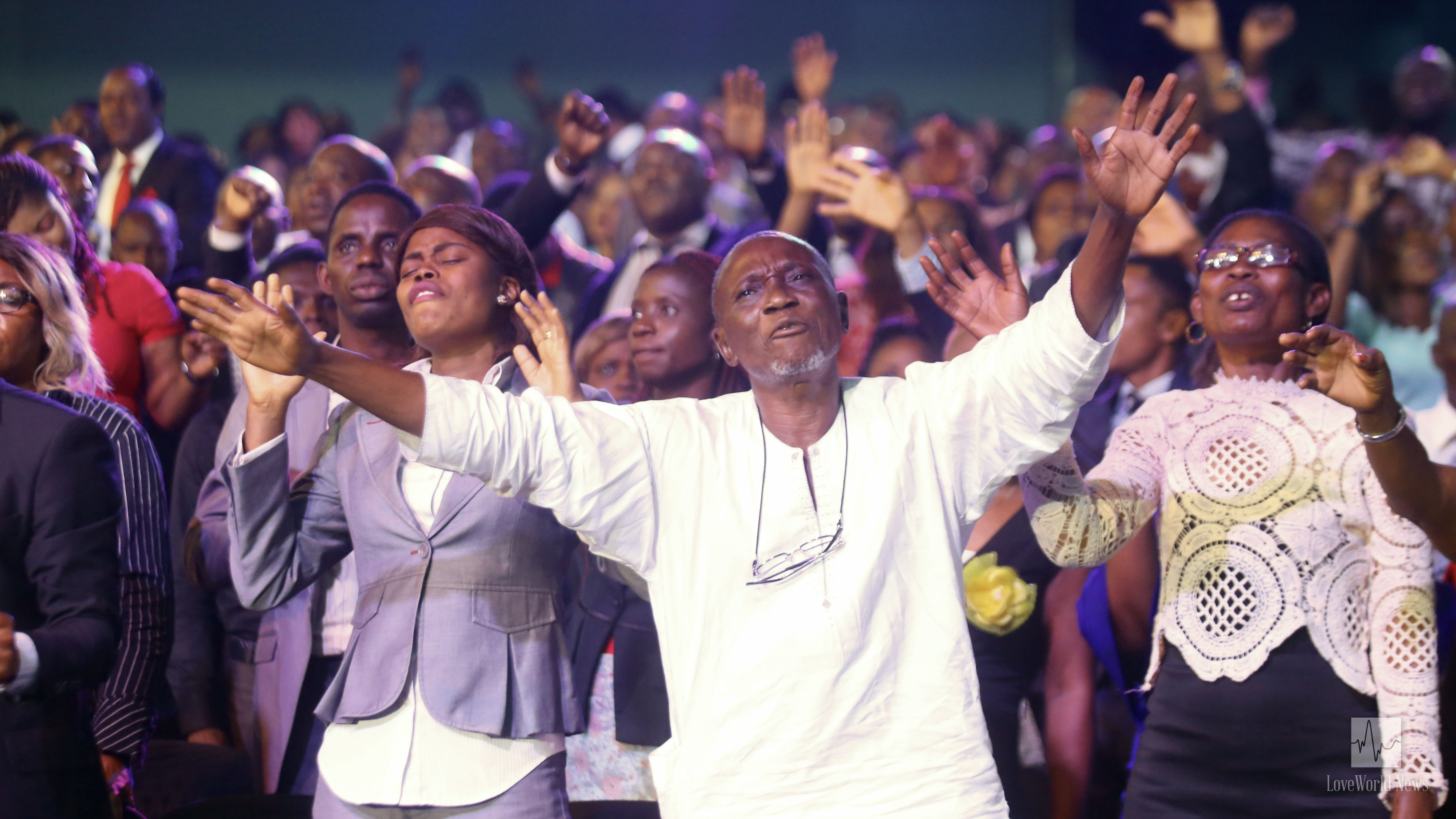 The people worship with hands lifted high.